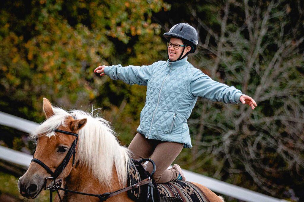 Jeune femme à genoux sur un cheval durant un cours de voltige