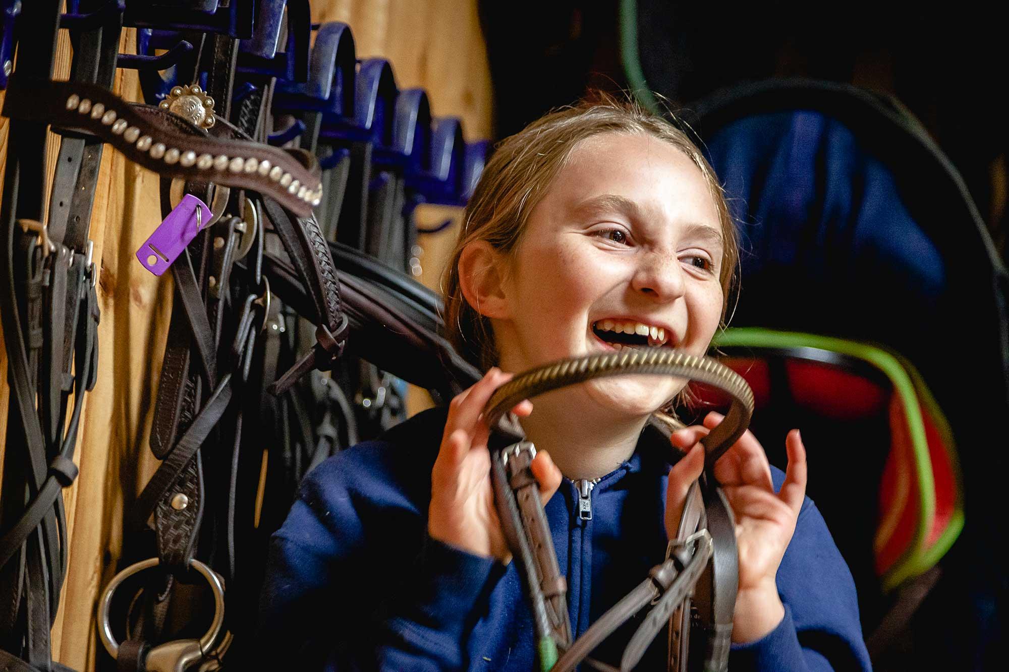Jeune fille qui s'amuse avec un harnais de cheval