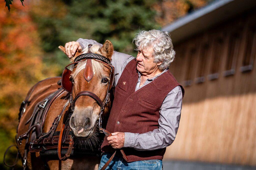 Homme ajustant le harnais de son cheval